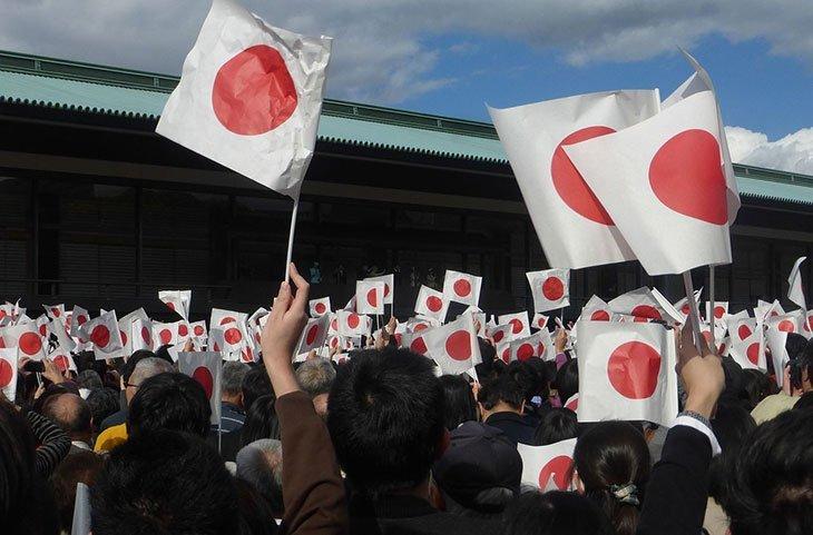 Les Japonais qui agitent des pays du Japon lors d'une manifestation de l'empereur Akihito