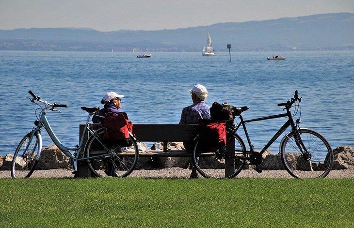 Des personnes âgées devant un lac, sur un banc